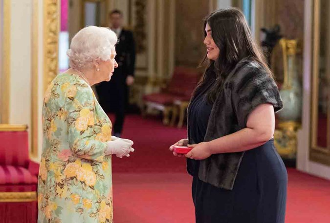 Caitlin meeting Her Majesty The Queen at Buckingham Palace